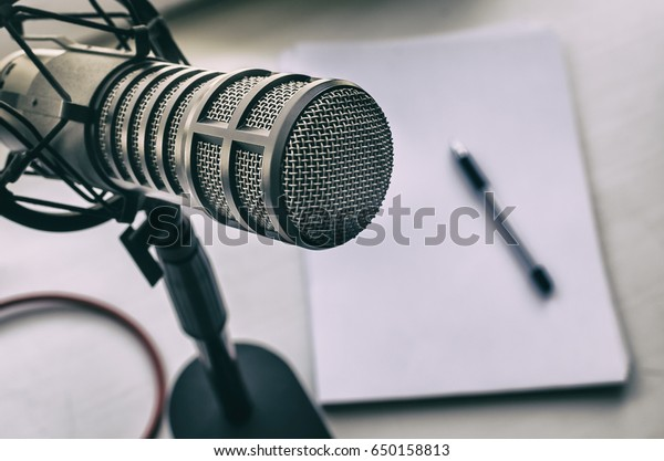 Microphone, sheets of paper and pen