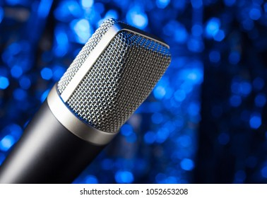 Microphone with silver mesh on a dark blue background