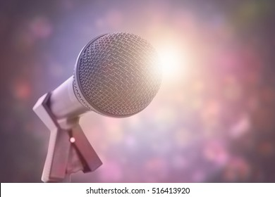 Microphone with stand against purple abstract light spot design