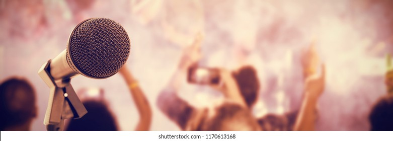 Microphone with stand against rear view of fans enjoying music concert