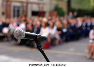 Microphone and stand in front of graduation ceremony audience against a background of auditorium and empty space for text