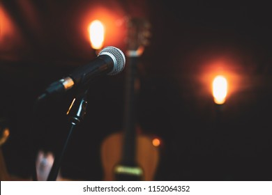 Microphone in studio against the background of acoustic guitar and vintage lighting