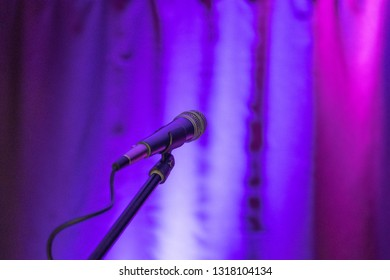 the microphone is turned on a multi-colored background, the background curtain is illuminated by different colored lamps