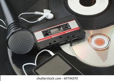 Microphone, vinyl discs, audiotape, mp3 player, cd over black