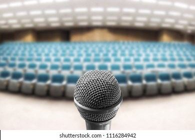 Microphone voice speaker over the blur photo of empty seminar room, lecture hall or conference meeting room background.Use for Education,Business event, teacher, or coaching mentor.