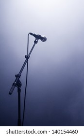 Microphone waiting for a voice in silhouette on a stage