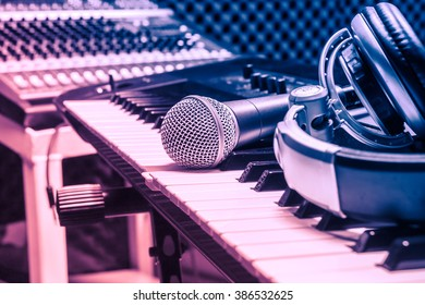 microphone,headphone on piano background.Blurred sound mixer.