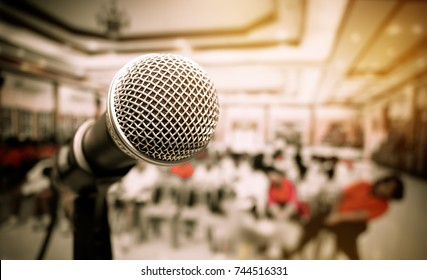 Microphones and computer notebook on front stage in seminar room, talking speech in conference hall light with microphone and keynote, blur light of meeting room background, vintage tone