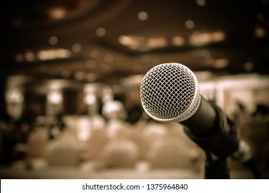 Microphones on abstract blurred of speech in seminar room or front speaking conference hall, blure light people in event meeting convention hall background, close up shot for copy space, Vintage tone
