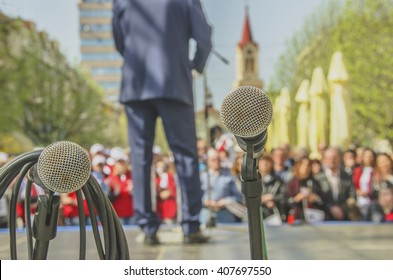 Microphones at political rally with leader and audience in the background