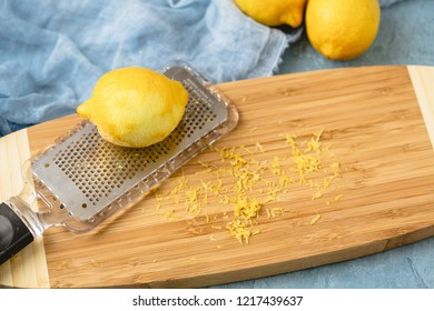 Microplane with fresh lemon making lemon zest on wooden board against a blue background.