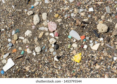 Microplastics pollution washed up on sandy beach, view from above