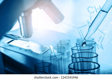 microscope and dropping chemical liquid to test tubes with lab glassware, science laboratory research and development concept in blue tone.