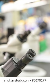 microscope eyepieces in a lab, with out of focus lab equipment backdrop