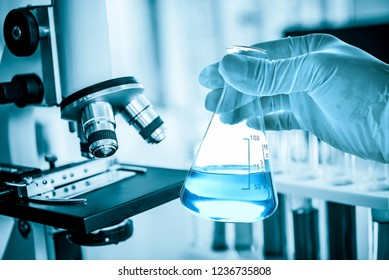 microscope with hand of scientist holding flask with lab glassware in laboratory background, science laboratory research and development concept