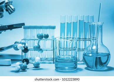 microscope and laboratory test tube on light blue background , science research equipment concept