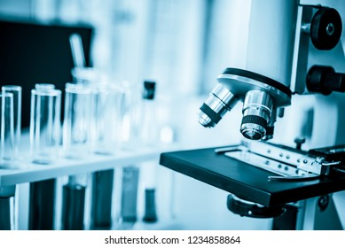 Microscope in microbiology lab with laboratory glassware background for medical research or science development concept.