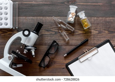 Microscope, pills and tablet on wooden background top view