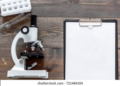 Microscope and tablet on wooden background top view.