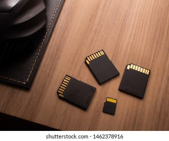 Microsd card, technology products. Photograph of three adapters and a micro sd card on a wooden object.