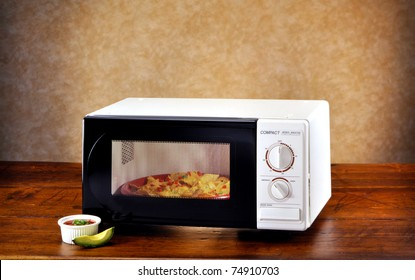 Microwave with nachos and avocado on wood set