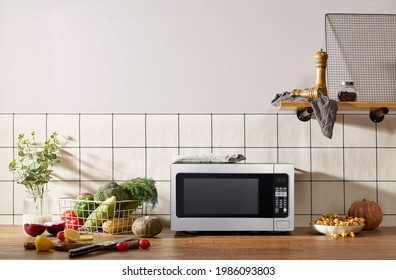 Microwave on kitchen table with vegetables