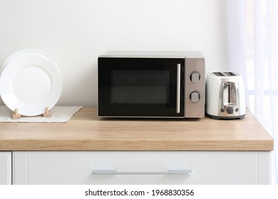 Microwave oven with toaster on kitchen table