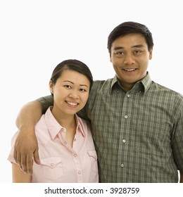 Mid adult Asian couple with arms around eachother smiling.