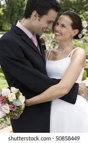 Mid adult bride and groom in garden, embracing