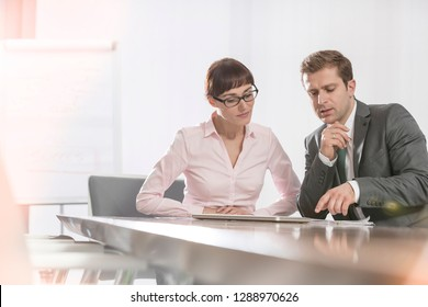Mid adult business colleagues discussing while sitting at conference table in boardroom