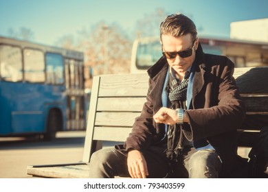 Mid adult businessman checking the time on his wristwatch while waiting on bus station.