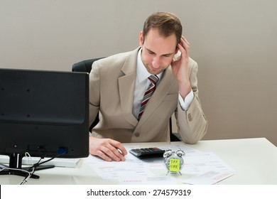 Mid Adult Businessman With Envelop And Alarm Clock At Desk