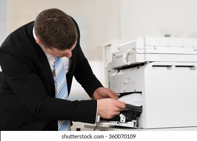 Mid adult businessman removing paper stuck in printer at office