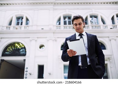 Mid adult businessman standing in big light hall holding tablet pc in the hands, happy business man reading news standing in the big railway station on the way to work, business people and finance