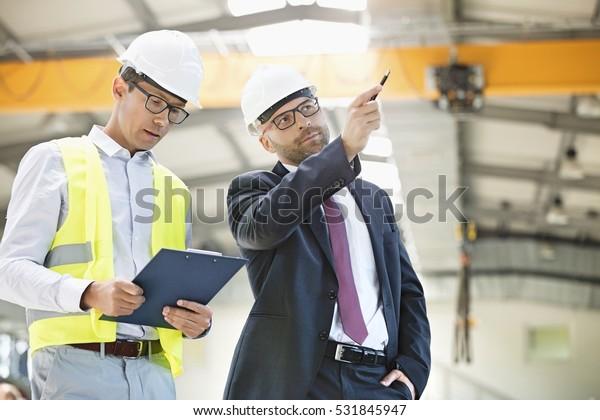 Mid dorosły biznesmen z przełożonym o dyskusji w przemyśle metalowym