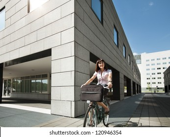 mid adult caucasian business woman commuting to office by bike and smiling