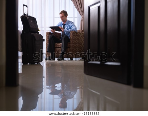 Mid adult caucasian manager typing on tablet pc in hotel room during business travel. Low angle view, full length