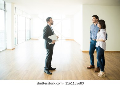 Mid adult couple with real estate agent visiting new house