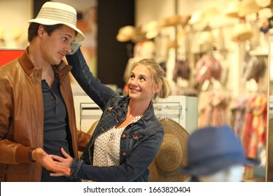 Mid adult couple trying on hat in clothes store, Munich, Bavaria, Germany, Europe