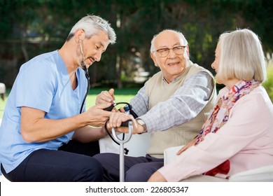 Mid adult doctor measuring blood pressure of senior man sitting beside woman at nursing home porch
