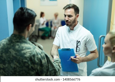 Mid adult doctor and military officer shaking hands while standing in a hallway at the hospital.