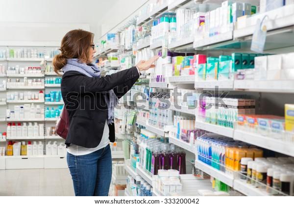 Mid adult female customer choosing product at pharmacy