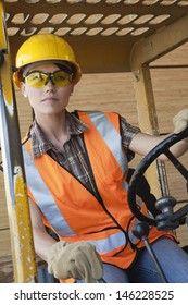 Mid adult female industrial worker driving forklift truck