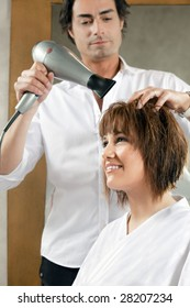 mid adult hairstylist drying woman hair. Side view