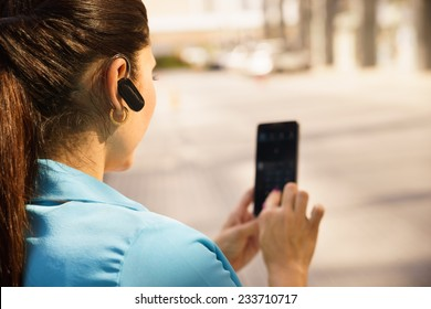 Mid adult hispanic person with mobile phone and bluetooth headset, typing on telephone in the street