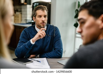 Mid adult insurance agent talking to a couple while having a meeting at their home.