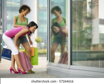 mid adult italian woman and hispanic woman looking at shop window with shopping bags. Horizontal shape, full length, copy space