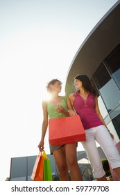 mid adult italian woman and hispanic woman carrying shopping bags out of shopping center at sunset. Vertical shape, low angle view, copy space