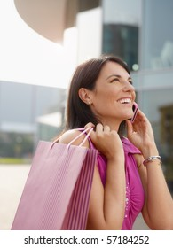 mid adult italian woman talking on mobile phone out of shopping center. Vertical shape, head and shoulders, copy space