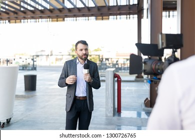 Mid adult male newscaster presenting business report in front of camera outdoors